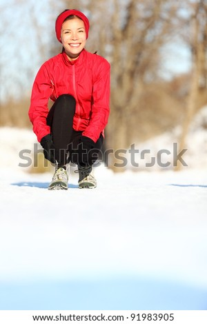 Winter runner getting ready running tying shoe laces. Beautiful young mixed race Asian / Caucasian female fitness model training outside. Copy space on snow. - stock photo