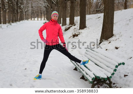 Winter running in park: happy woman runner warming up and exercising before jogging in snow, outdoor sport and fitness concept  - stock photo