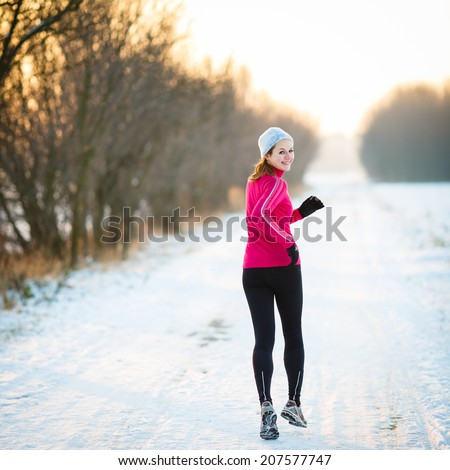 Winter running - Young woman running outdoors on a cold winter day - stock photo