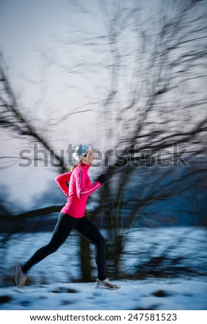 Winter running - Young woman running outdoors on a cold winter day (motion blurred image, color toned image) - stock photo