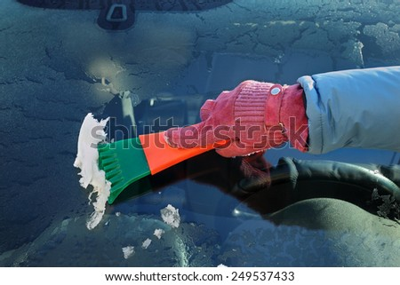 Winter scene, human hand in glove scraping ice from windshield of car - stock photo