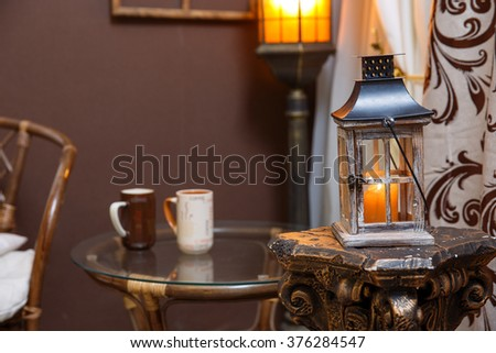 Winter scene. Living room, mugs, candle on the table. - stock photo