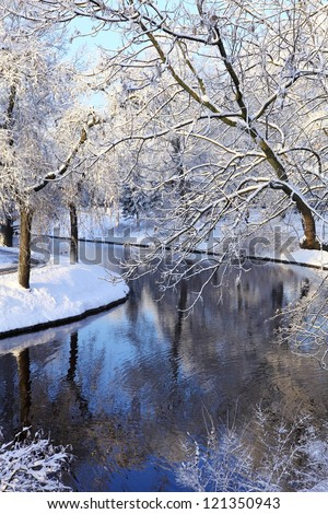 winter scene of a channel and trees - stock photo