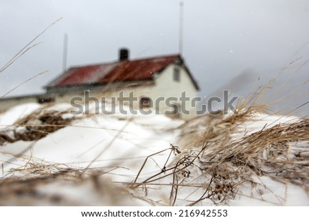 Winter scene with dry grass, covered with snow, and small lonely house in Raufarhofn village in northern Iceland - stock photo