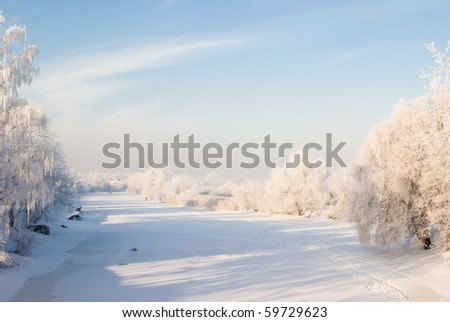 Winter scene with snowy trees and river covered with ice - stock photo