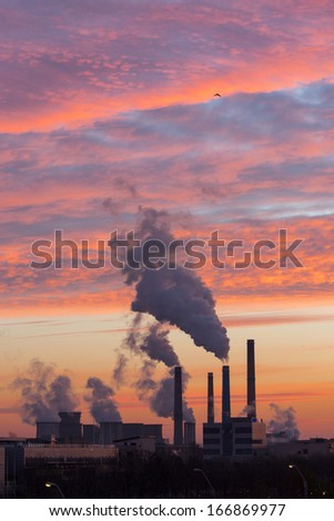 Winter scenic of power plant with a burning red clouds behind - stock photo