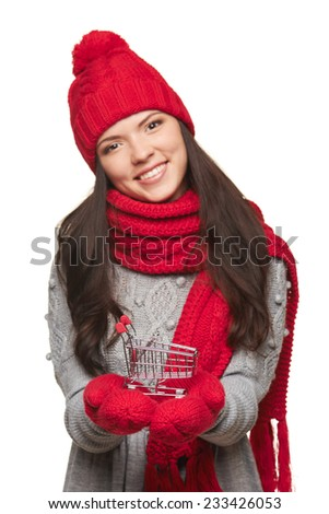 Winter shopping concept. Smiling beautiful woman in winter red hat and scarf showing small empty shopping basket over white background. Shallow depth of field, focus on basket - stock photo