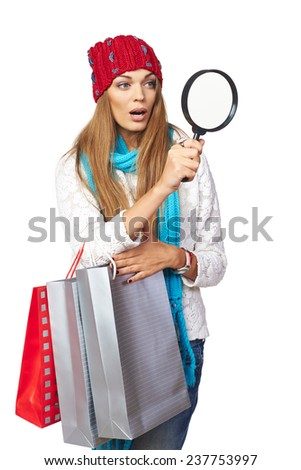Winter shopping search concept. Surprised beautiful woman in winter hat and scarf holding shopping bags and searching through magnifying glass, over white background - stock photo