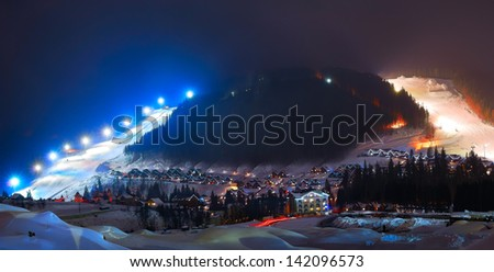 Winter ski resort at night in the mountains - stock photo