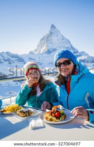Winter, ski - skiers enjoying break for lunch - stock photo
