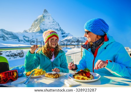 Winter, ski - skiers enjoying break for lunch, mountain view Matterhorn - stock photo