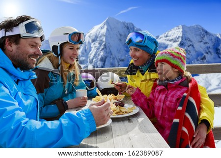 Winter, ski - skiers enjoying lunch in winter mountains - stock photo