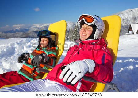 Winter, ski, sun and fun - Portrait of mother with her daughter in winter resort resting in the deck chair - stock photo