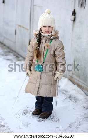 Winter small girl with long hair holds big icicle on grey industrial background - stock photo
