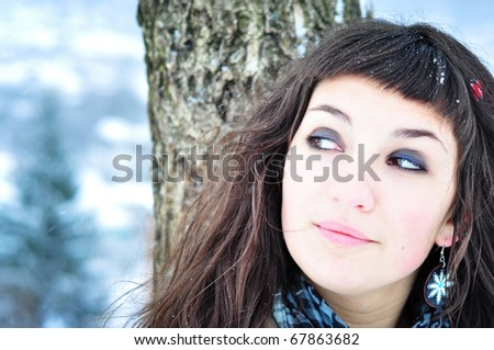 Winter smile. Happy girl in winter forest, smiling looking sideways - stock photo