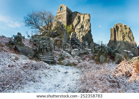Winter snow at Roche Rock an outcrop of craggy granite with an ancient ruined chapel built in to the rock on moorland at Roche near St Austell in mid Cornwall - stock photo