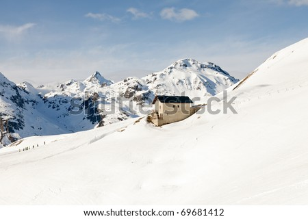 Winter snow mountains with cottage and blue cloudy sky - stock photo