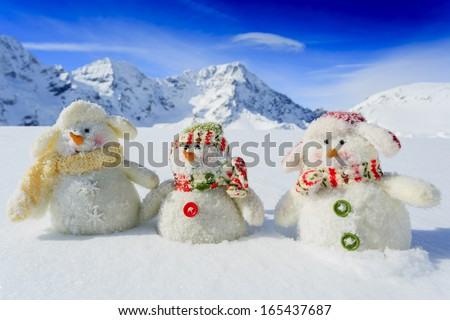 Winter, snow, sun and fun, Christmas - happy snowman friends and snowy mountains in background - stock photo