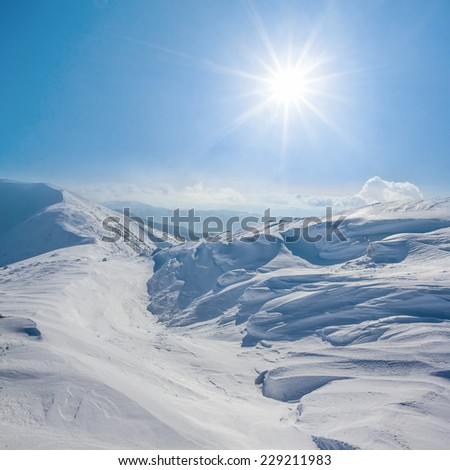 winter snowbound hills under a sparkle sun - stock photo