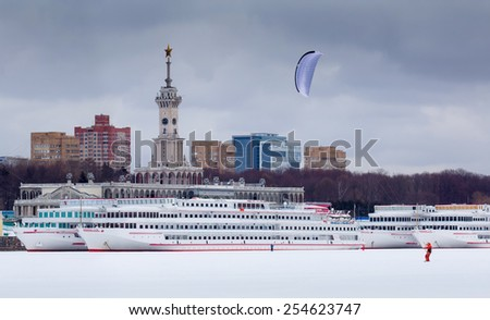 Winter snowkiting at Moscow North River Port and ships behind kiteboarder   - stock photo