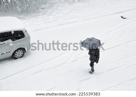 Winter snowy city scene with pedestrian and car. - stock photo