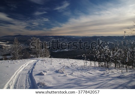 Winter snowy mountains and the track of the snowmobile in the foreground under blue sky. Altai Mountains, Siberia, Russia - stock photo