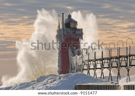 Winter South Haven, Michigan Lighthouse with crashing wave, Lake Michigan, USA - stock photo