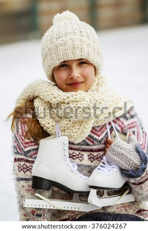 Winter sport, girl with a pair of ice skates - stock photo