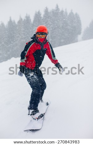 Winter sports. Young woman snowboarder going down the slope on snowy day - stock photo