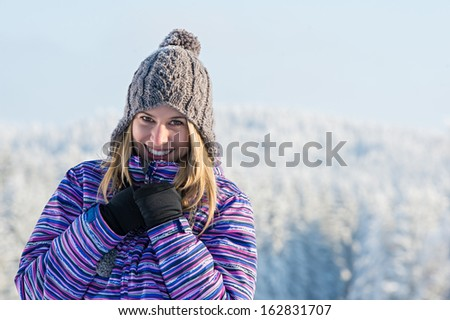 Winter sporty woman portrait snow mountains smiling at camera - stock photo