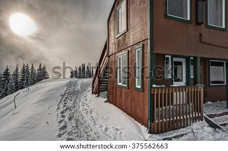 Winter Sun Warms European Style Alpine Snow Hut  - stock photo