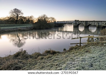 Winter sunrise landscape over river and fields covered in frost - stock photo