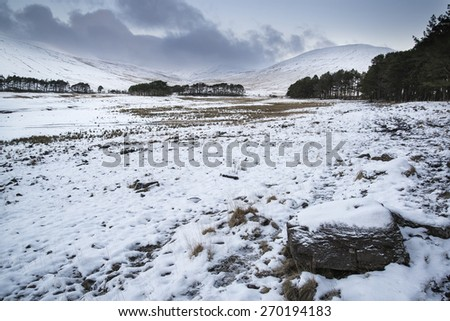 Winter sunrise over mountain range landscape with snow covered ground - stock photo