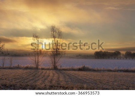 Winter sunset over farm land with trees in Idaho - stock photo