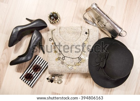 Winter sweater and accessories arranged on the floor. Woman sweater with silver accessories, high heels, hat, necklace and nail polish. - stock photo