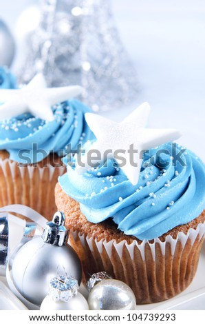 Winter theme christmas cupcakes with blue frosting and silver christmas ornaments - stock photo