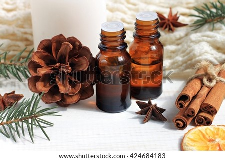 Winter time cozy scents essential oil aroma blend. Conifer, orange, cone, anise, cinnamon. Warming essential oils bottles. - stock photo