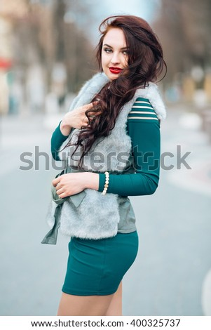Winter time fashion for women. Woman wearing sweater fur vest belt and pendant in freezing cold time. - stock photo