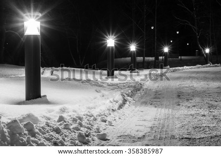 Winter-time footpath illuminated by modern lanterns, black and white image - stock photo