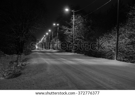 Winter-time snowy rural road, black and white image - stock photo