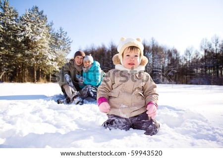 Winter toddler and her parents in a park - stock photo