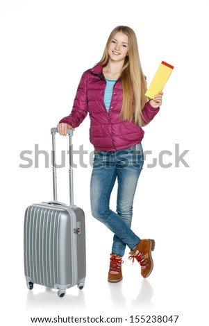 Winter traveler. Full length of young female in winter jacket standing with the suitcase showing blank tickets, isolated on white background - stock photo