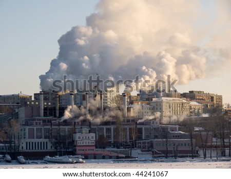 Winter urban landscape. From pipe factory fells smoke into the blue sky. - stock photo