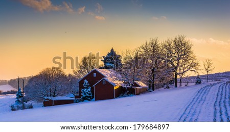 Winter view of a barn on a snow covered farm field at sunset, in rural York County, Pennsylvania. - stock photo