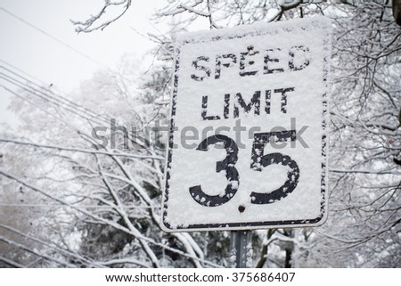 winter warning sign shows speed limit of ice and snow at street, highway or road - stock photo