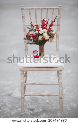 Winter wedding bouquet with pine cones and red and white flowers on a chair with a ring - stock photo
