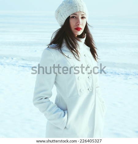 Winter weekend at the seaside concept. Emotive portrait of fashionable model in white coat and beret looking at camera. Sunny weather. French street fashion style. Outdoor shot - stock photo
