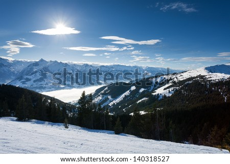 winter with ski slopes of kaprun resort next to kitzsteinhorn peak in austrian alps - stock photo