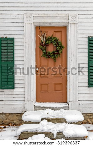 Winter Wreath on Brown Door with Snow on Steps - stock photo