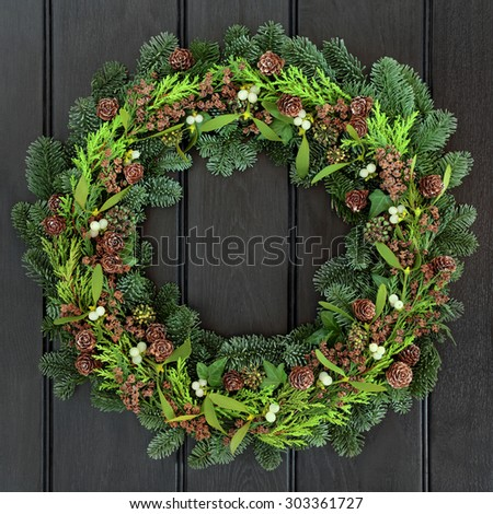 Winter wreath with mistletoe and blue spruce fir over dark blue oak front door background. - stock photo